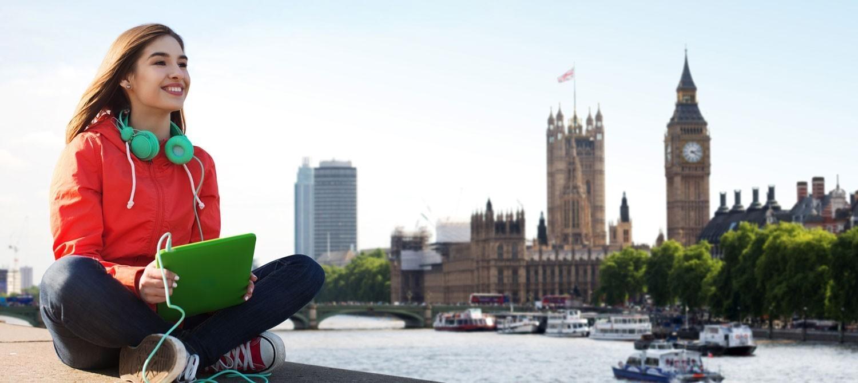 Chica joven sentada con su tablet, frente al Big Ben en Londres